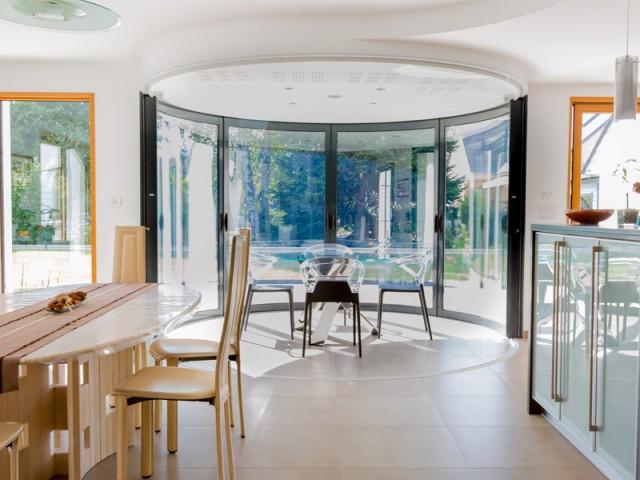 Gain de lumière et de chaleur - Une salle à manger dedans/dehors avec vue panoramique sur l'extérieur