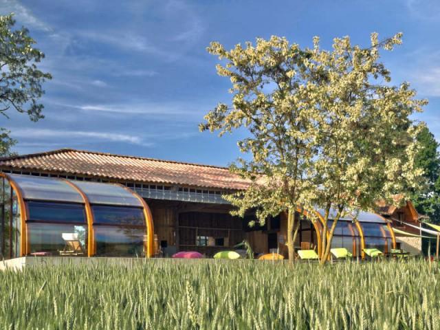 Une esthétique naturelle - Un abri de piscine sur un hangar rustique