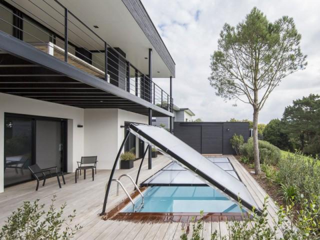 Un abri piscine en harmonie avec la maison - Un abri plat discret et moderne