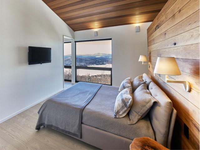 Une chambre parentale ouverte sur l'extérieur - Chalet contemporain sur pilotis entre la forêt et les lacs
