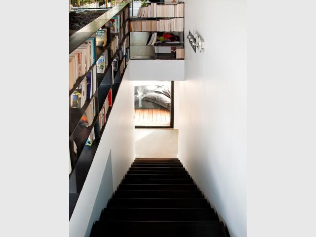 Un escalier/bibliothèque en acier brut - Une maison construite entre les arbres