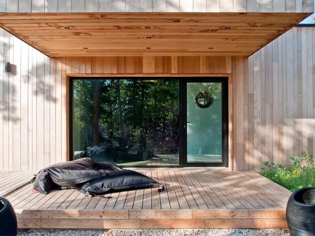 Un porte à faux utilisé comme protection solaire - Une maison construite entre les arbres