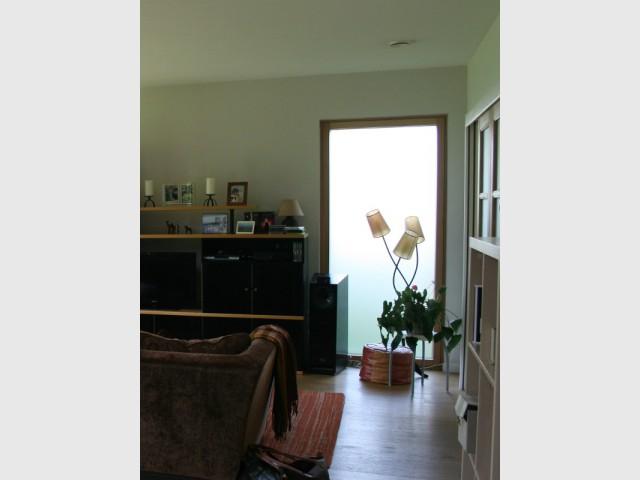 Une fenêtre dépolie dans le salon pour un apport de lumière supplémentaire  - Une maison passive en bois bâtie dans la forêt