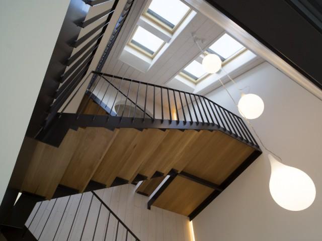 Un escalier moderne et élégant inondé de lumière  - Une maison comme un mille-feuille de bois