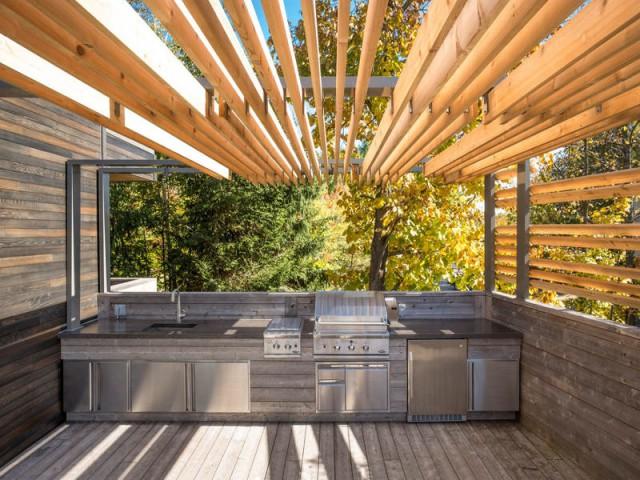 Une cuisine d'extérieur équipée aux teintes vieillies - Une terrasse en cèdre magnifie le paysage canadien