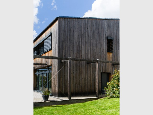 Une porte d'entrée dissimulée dans la façade de la maison passive - Une maison passive en bois gris au coeur des Yvelines