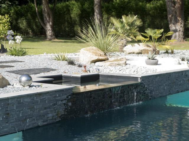 Un spa à débordement intégré au muret en ardoise  - Une piscine équipée d'une fosse de plongée