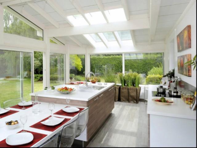 Une table accolée à un îlot central pour une cuisine élégante - Une vraie table de repas dans la cuisine