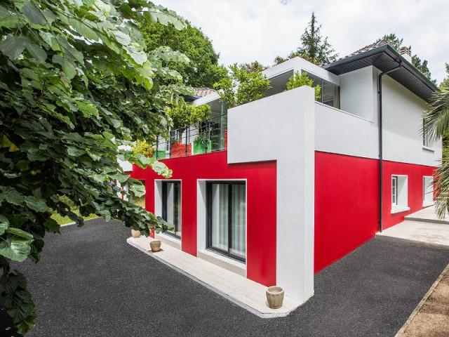 Une isolation thermique par l'extérieure efficace - un rouge flamboyant pour la façade d'une maison