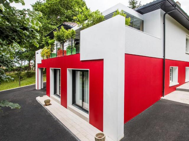Des jambages blancs intégrés à une maison basque pour un style très moderne  - un rouge flamboyant pour la façade d'une maison