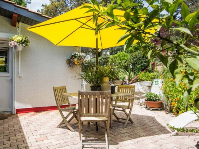 Un petit jardin à l'abri du soleil - un rouge flamboyant pour la façade d'une maison