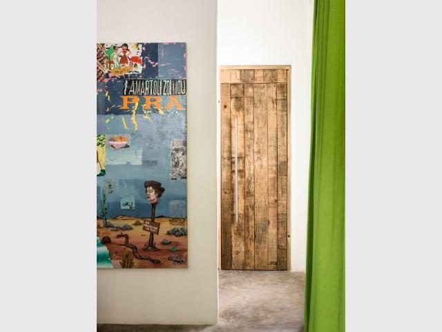 Une porte effet bois vieilli épouse un mur blanc - Dix idées à copier pour son intérieur.