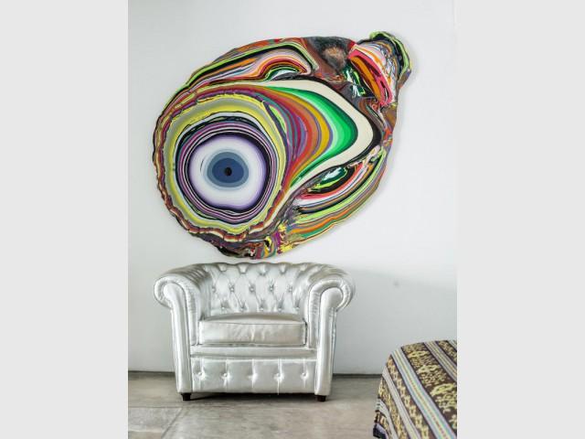 Une oeuvre d'art trône au dessus d'un fauteuil pour attirer le regard - Dix idées à copier pour son intérieur.