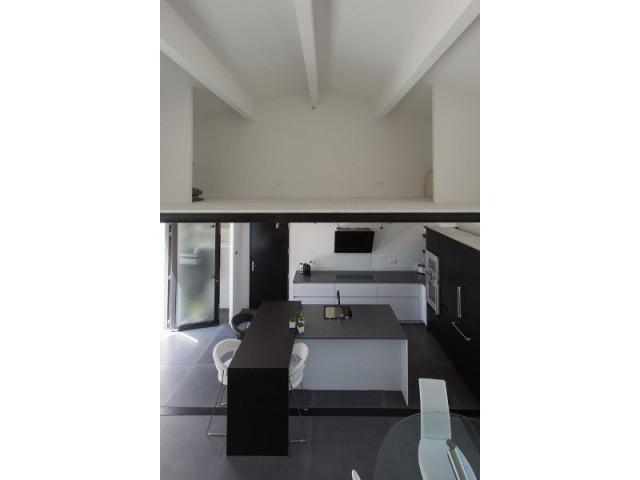 Un plafond cathédrale et une cuisine noir et blanc - Maison individuelle Rouvière Construction
