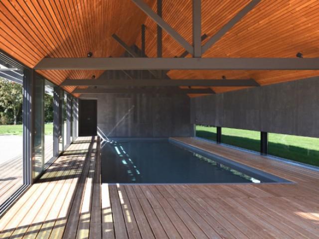 Un pignon entièrement en panneaux composite pour homogénéiser la pièce - Un abri de piscine inspiré des hangars agricoles