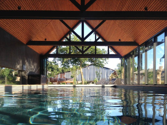 Une importante hauteur sous-plafond pour agrandir l'espace - Un abri de piscine inspiré des hangars agricoles