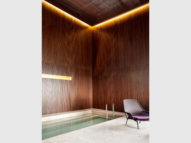 Une piscine couverte sous un plafond de bois