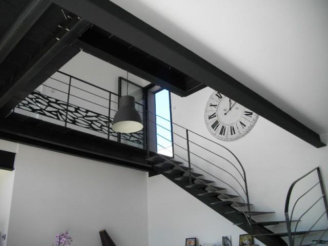Un escalier en métal noir et un vide sur séjour