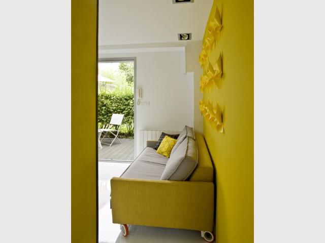 Un mur jaune moutarde apporte chaleur et poésie à la pièce de vie - Un appartement de bord mer lumineux et chaleureux