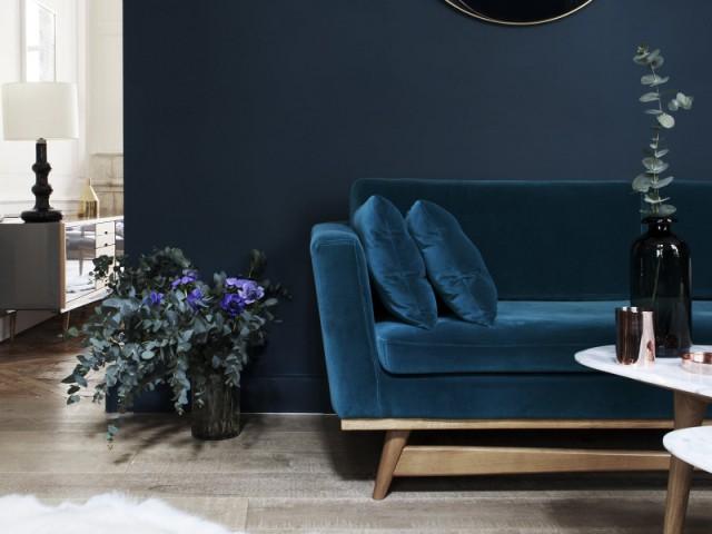 Un canapé en velours bleu vert pour un salon végétal