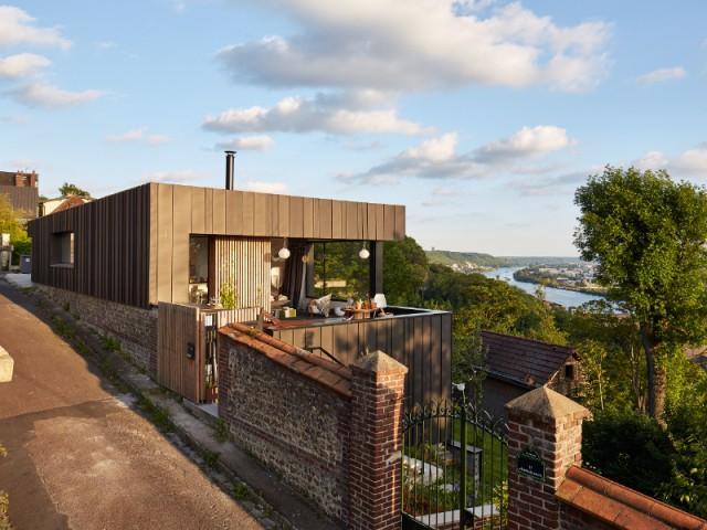 Une maison posée sur un mur en brique - Une maison en zinc noir posée sur un mur en brique