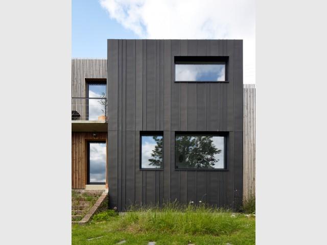 Une enveloppe en zinc noir - Une maison en zinc noir posée sur un mur en brique