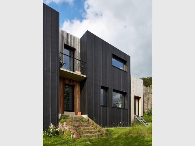 Du bois pour distinguer certaines zones - Une maison en zinc noir posée sur un mur en brique