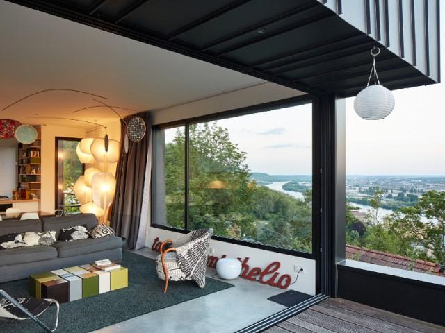 Fiche technique :  - Une maison en zinc noir posée sur un mur en brique