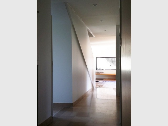 Un couloir d'entrée trop grand, rendu plus intime par un escalier
