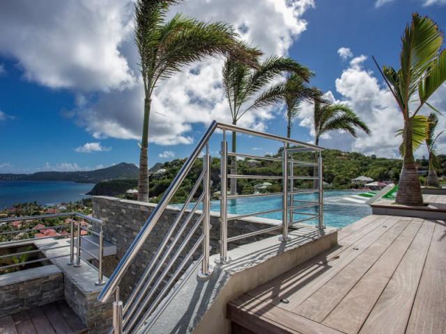 Une terrasse avec une piscine à débordement
