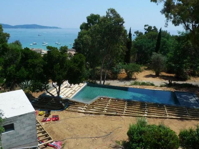 Une piscine enveloppée par une terrasse en bois