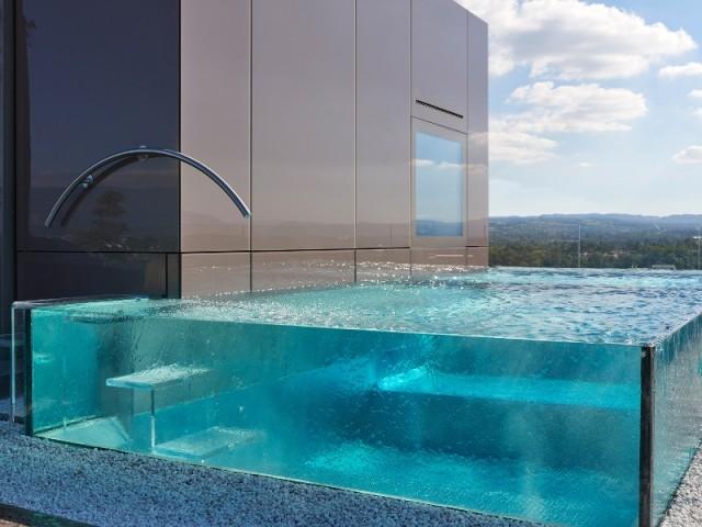 Une piscine aux parois de verre posée sur un toit