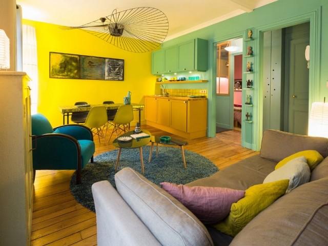 Un séjour double avec cuisine ouverte turquoise et jaune