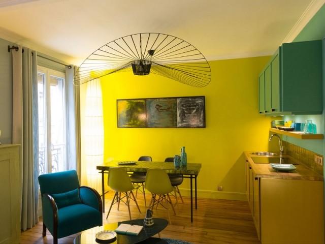 Une cuisine turquoise et jaune avec coin salle à manger