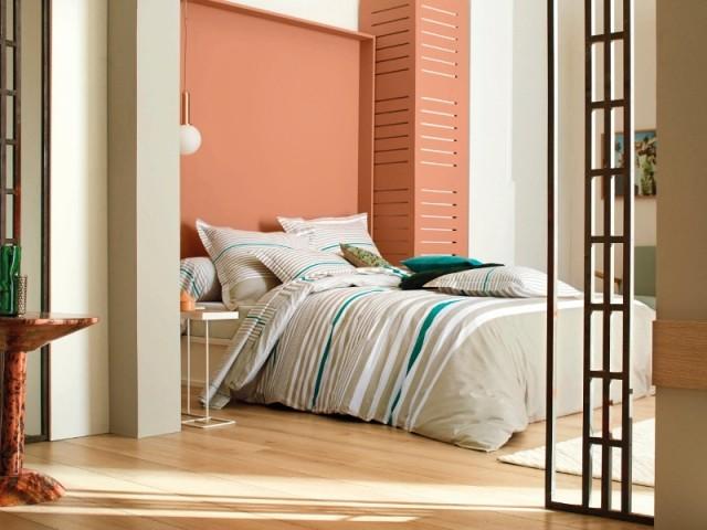 Un lit dans une alcôve pastel