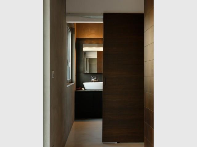 Une salle de bains cachée derrière des portes coulissantes en noisetier