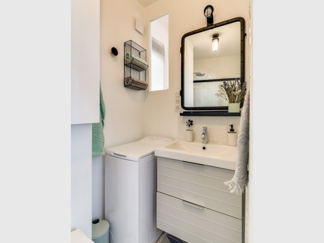 Une petite ouverture vitrée dans la salle de bains industrielle