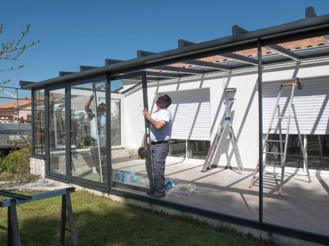 Pose des baies vitrées à trois vantaux de la véranda