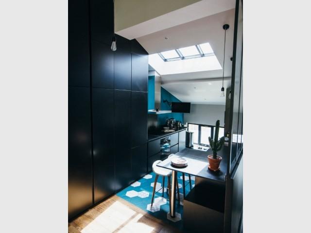 Une cuisine entre carreaux bleu et placards noir mat