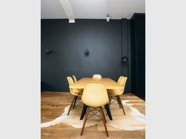 Une salle à manger aux murs noir mat