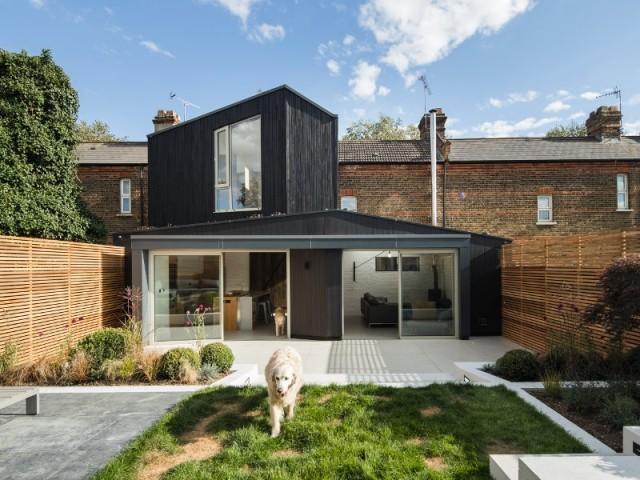 Une extension bois noir sur une maison en brique