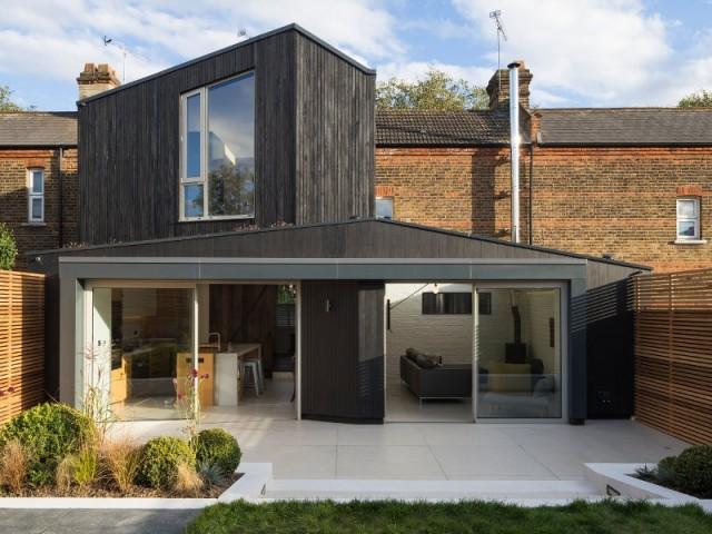 Une extension noire qui contraste avec la maison en brique