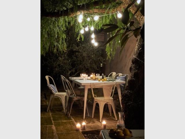 Bougies et guirlandes lumineuses pour une table de jardin cocon