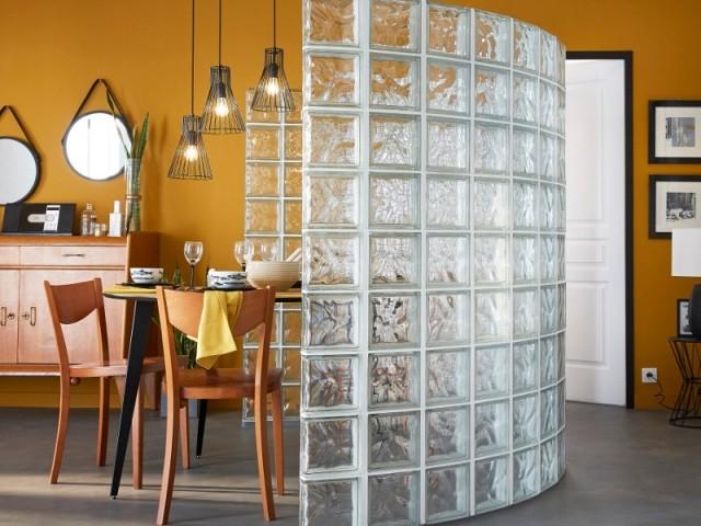 Une cloison courbe en brique de verre pour délimiter la salle à manger