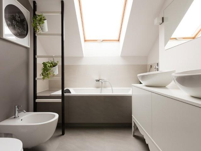 Une salle de bains avec baignoire positionnée sous les toits