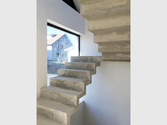 Un escalier en béton brut qui serpente au centre de la maison