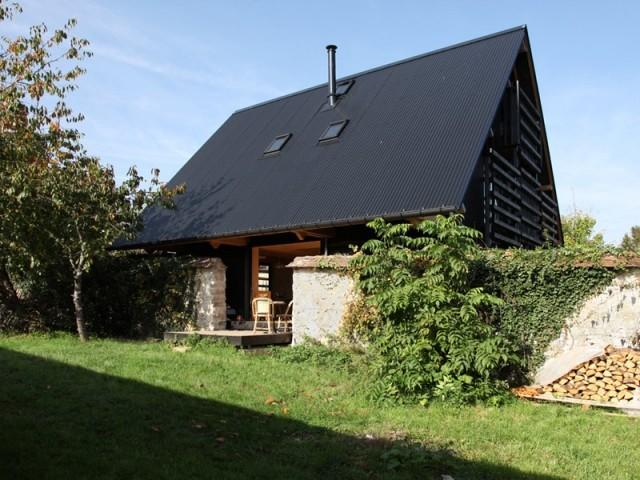 Une maison tout en bois blottie entre deux murs en pierres