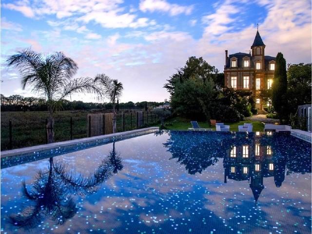 Vue nocturne d'une piscine sur 2 niveaux débordante