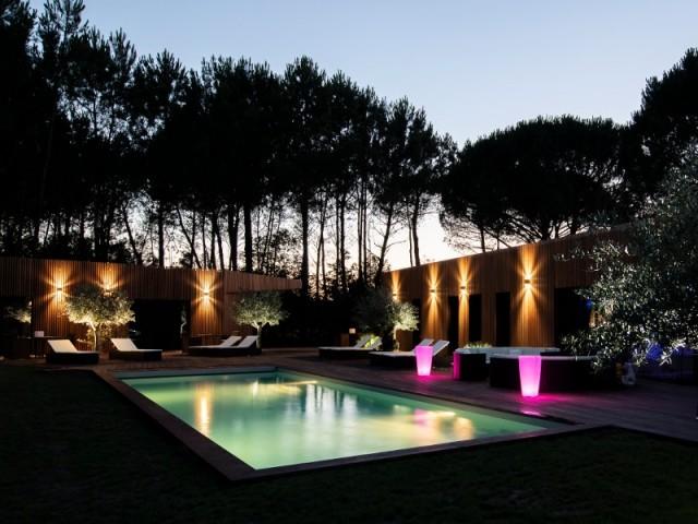 Vue nocturne d'une piscine construite en bloc à bancher avec revêtement PCV armé gris perle