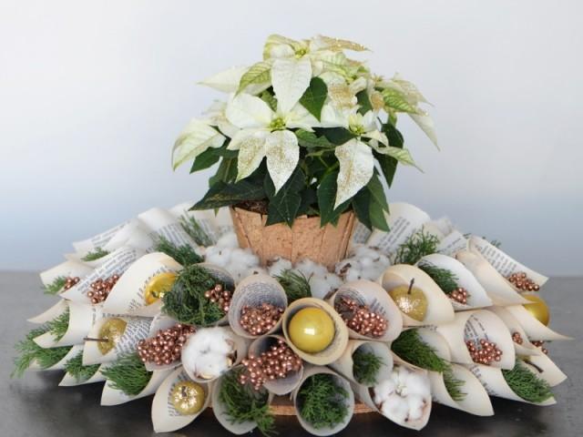 Un centre de table fleuri d'un poinsetia et décoré